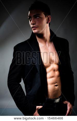 young handsome muscular man in the dark, studio shot
