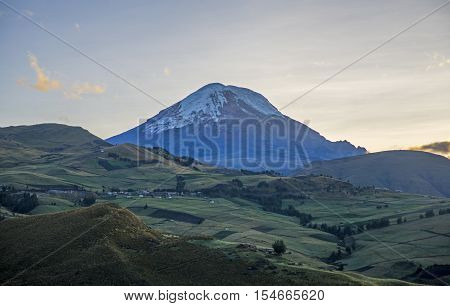View of the Chimborazo volcano in semi silhouette and surrounding Andes mountains, on a sunny morning. Bolivar Province, Ecuador