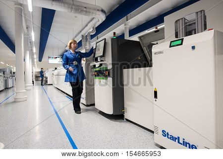 Saint-Petersburg Russia - November 2 2016: Manufacturer of automotive security systems Starline. Operator woman on the production line for the production of chips for car alarms.