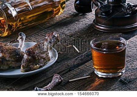 Glass and laying bottle of whiskey with half-eaten roasted chicken pieces on the rustic wooden table