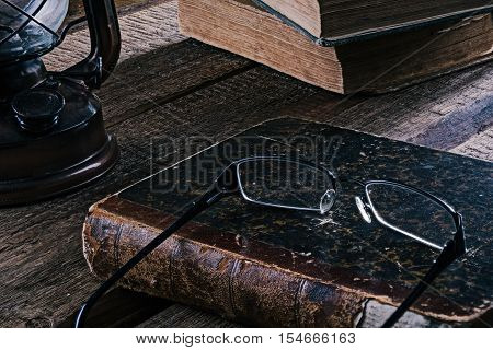 Slill-life with books, lamp and eyeglasses on the rustic wood table