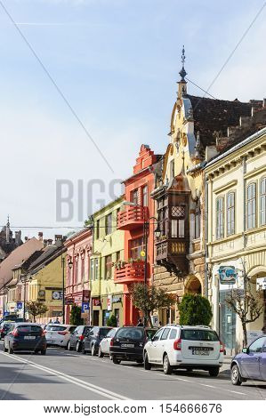 Sighisoara, Romania - October 19th, 2016: View of modern streets with people and cars of medieval Sighisoara, Transylvania region, Romania
