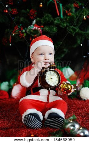 Child dressed as Santa Claus gnawing teeth clock alarm clock. Child dressed as Santa sitting on the background of the Christmas tree