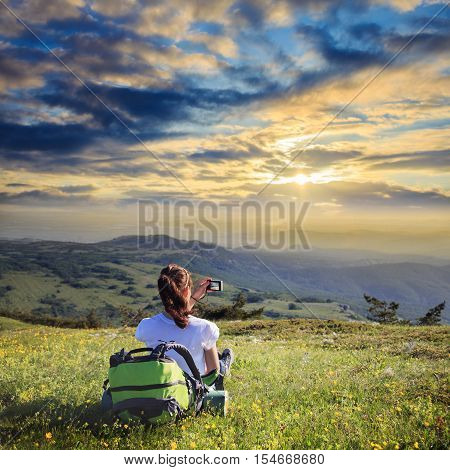 Young female traveller with backpack and long brown hair sitting at green grass glade and making photo of mountain lanscape in summer day under sunset sky