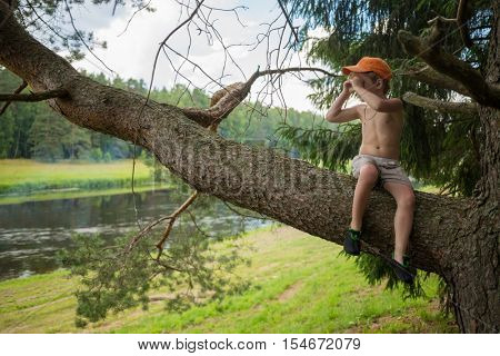 Little cute boy sits on tree branch and looks away near river at summer