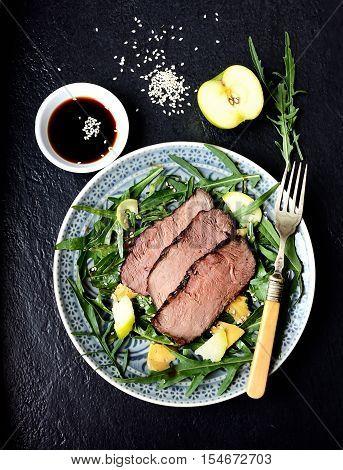 salad of arugula and roast beef on a black background