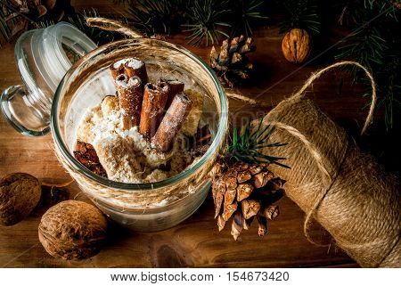 Original idea for a Christmas gift: a set of dry ingredients for ginger cookies, decorated in a jar, on a background of branches of the Christmas tree, cones, nuts.