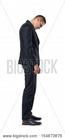 Businessman stands in profile hanging his head , isolated on a white background. Difficulties at work. Problems and issues. Predicament. Necessity to decide. Confusion and doubt.