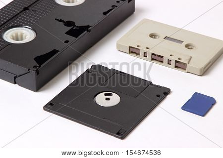 videocassette audio cassette computer diskette and flash drive on white background