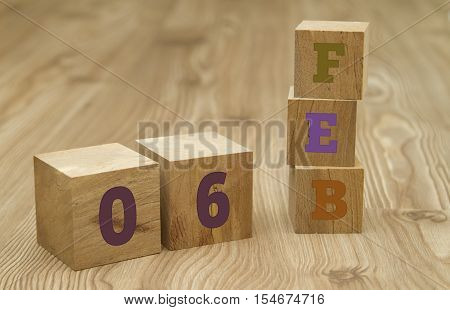 Cube shape calendar for February 06 on wooden surface with empty space for text. poster