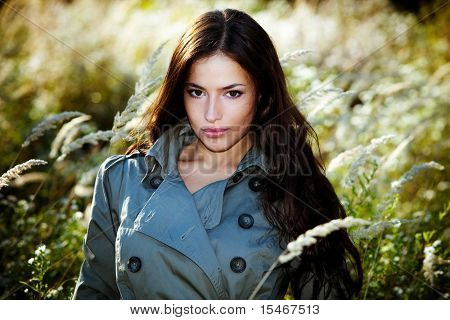 young woman in topcoat walking accros the autumn meadow