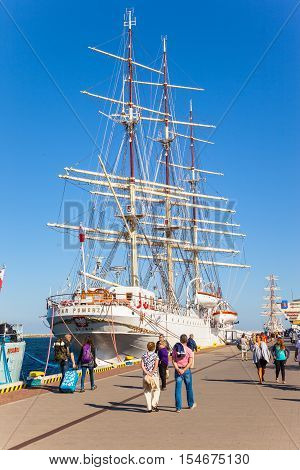 GDYNIA, POLAND - SEPTEMBER 17, 2016: People visit Polish training tall ship Dar Pomorza Kosciudzko square in Gdynia. The sailing frigate dating back to 1909 is a famous museum ship nowadays.