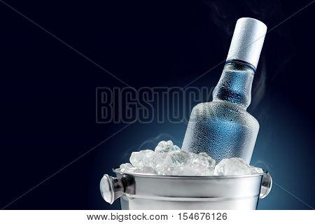 Bottle of cold vodka in bucket of ice on dark background