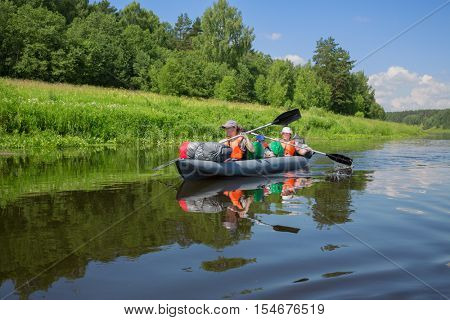 Two adults and boy in life jackets sail on inflatable boats during hike at summer