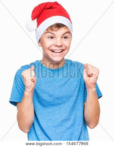 Half-length portrait of caucasian teen boy wearing Santa Claus hat. Teenager in blue t-shirt looking at camera. Holiday Christmas concept - happy cute child isolated on white background.