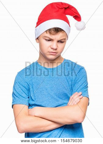 Half-length emotional portrait of caucasian teen boy wearing Santa Claus hat, sad. Teenager in blue t-shirt with arms folded. Holiday Christmas concept - unhappy cute child isolated on white background.