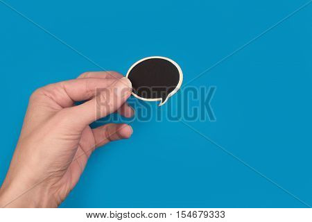 top view of hand holding a black wooden speech bubble on blue background