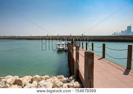 MANAMA, BAHRAIN - OCT 29, 2016: Visitors walking towards the boat along the bridge to visit the Bu Maher Fort in Arad from the Bahrain National Museum boat jetty