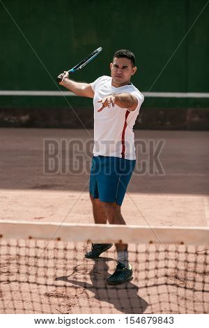 Handsome Young Man On Tennis Court. Man Playing Tennis. Man Hitting Tennis Ball
