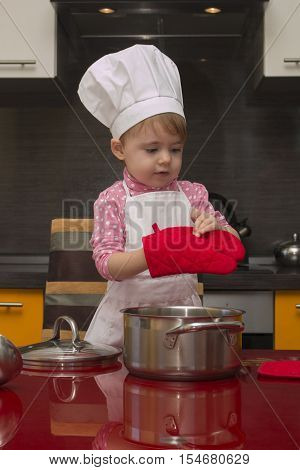 The little girl in a suit of the cook sculpts dough. Baby make dinner in chef suit