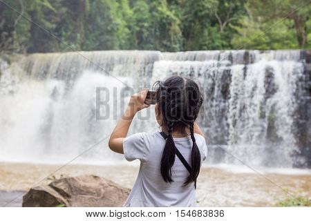 Asian kid with a waterfall in Thailand.