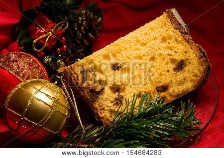 Good piece of homemade panettone - traditional sweet bread for Christmas and New Year with fruit and spices drizzled with icing sugar on dark holiday background with pine branch and Christmas decorations. Selective focus. Horizontal.