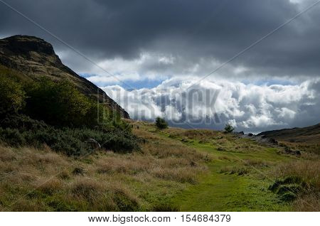 Cloudy skies above Arthur's Seat in Scotland.