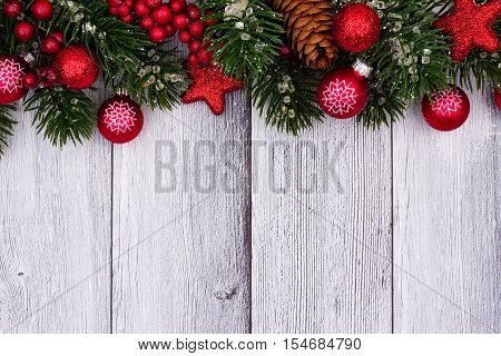 Red Christmas Ornaments And Branches Top Border On A Rustic White Wood Background
