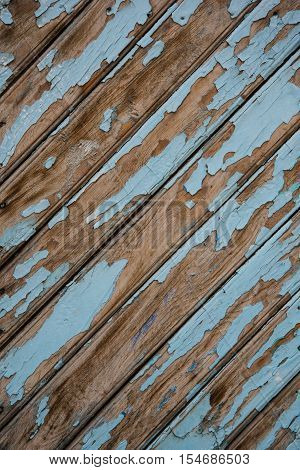 Ancient old wooden door with peeled blue paint.