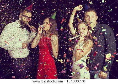 Two beautiful young couples having fun at New Year's party wearing party hats dancing and blowing party whistles