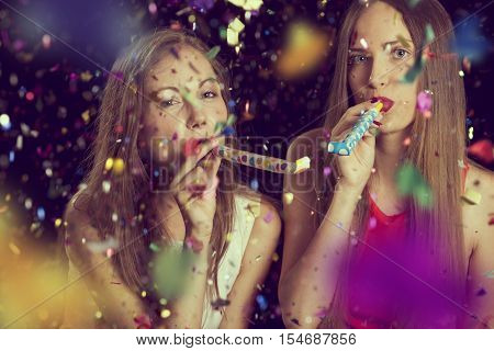Two beautiful girls having fun at New Year's party dancing and blowing party whistles. Focus on the girl in the white dress