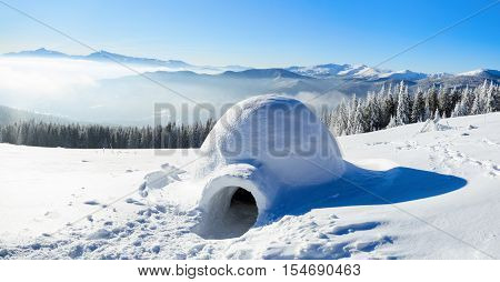 On the snow-covered meadow in the mountains stands a solitary igloo to which there lead a big trampled trail and many traces on a winter day.