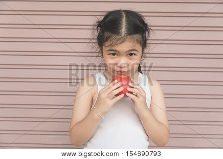 Little Asian Girl Enjoy Eat An Apple.