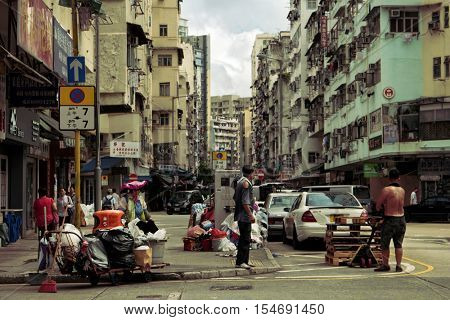 Hong Kong - October 2016: Kowloon street view with people. Lady recycling garbage and man carrying pallets. Retro look.