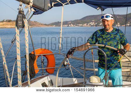 Man skipper steers boat sailing yacht on the Aegean Sea.