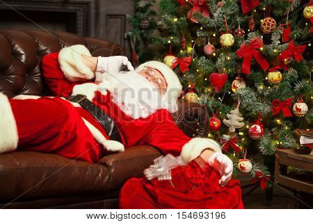 Santa Clause snoozing in a decorated living room with his sack full of gifts by his side. poster