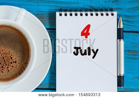 July 4th. Day of the month 4 , calendar on business workplace background with morning coffee cup. Summer concept. Empty space for text.