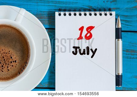 July 18th. Day 18 of month, calendar on business workplace background with morning coffee cup. Summer concept. Empty space for text.