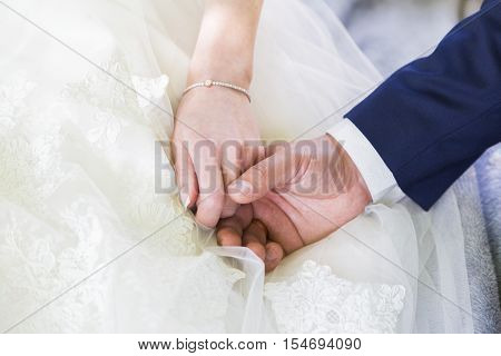 Groom in a blue suit and white shirt and bride in white wedding dress gently holding hands