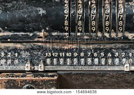 Old rusty mechanical retro black calculator close-up as background