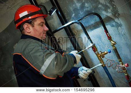 Plumber technician works with valve and pipes