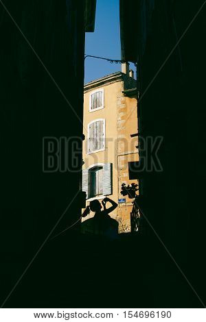 Silhouetted girl taking travel photos in french village