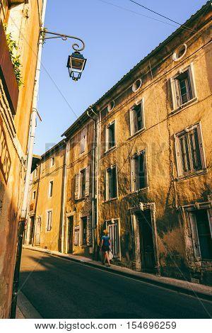 Woman walking through quiet Provence town Bonnieux