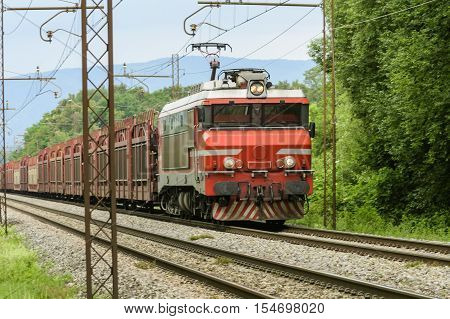 Red locomotive towing a freight train through woods