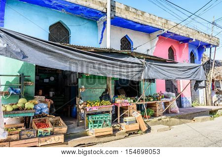 Livingston, Guatemala - August 31 2016: Shopkeeper sits inside colorful grocery store in Caribbean town of Livingston