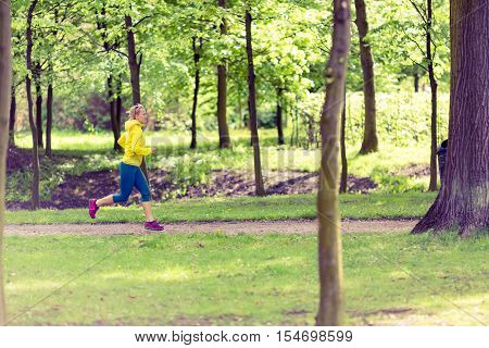 Woman running and walking in beautiful park. Young girl jogging in bright forest outdoors summer nature. Endurance concept with working out and exercising in inspirational green woods landscape.