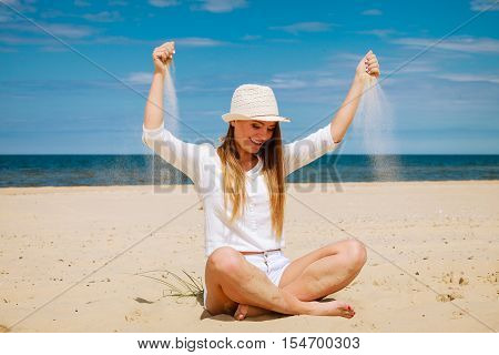 Happiness and craziness. Smiling crazy girl have fun with sand outdoor. Young attractive long haired woman playing on summer beach.