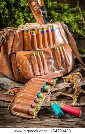 Cartridge belt and bag hunting on old wooden table