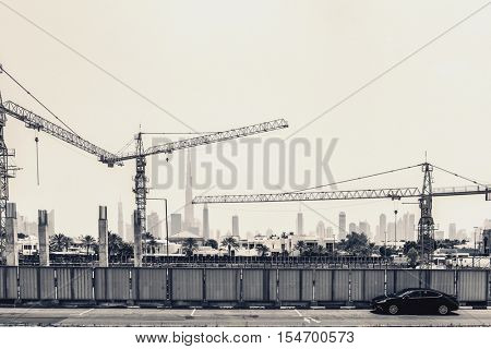 Dubai, U.A.E. - Circa August, 2016: Construction and development in Dubai, UAE with a street view of a building site with large industrial cranes with the city skyline in the distance