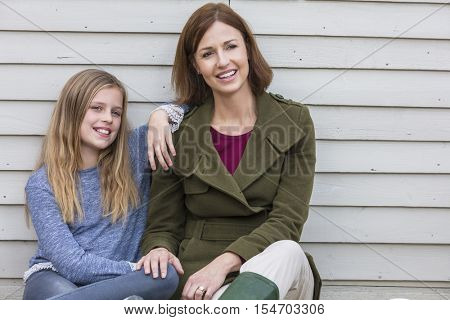 Portrait shot of an attractive, successful and happy middle aged woman female outside smiling with her female child daughter